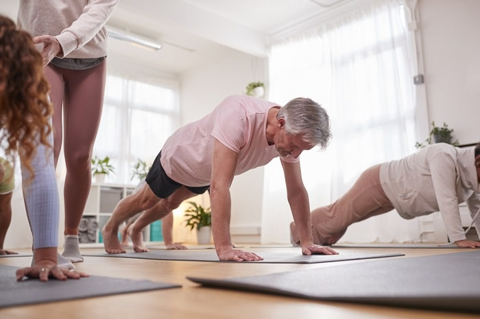 A senior man doing a plank pose during a yoga class.