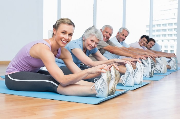 A yoga instructor and some seniors in her class with their shoes on during a session.
