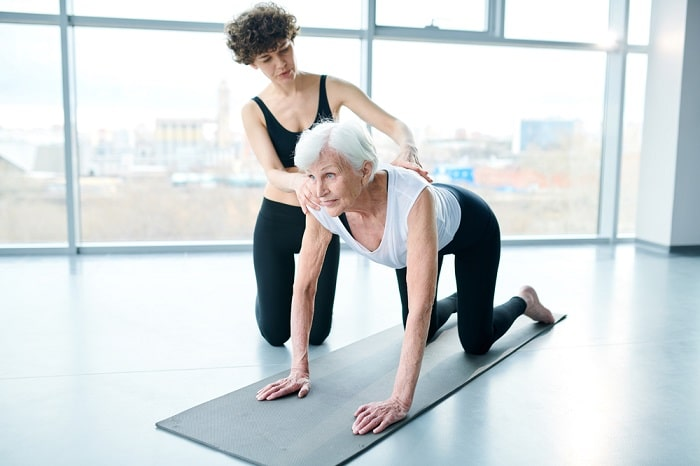 A yoga instructor assisting a senior woman to find her balance by focusing her eyes during an intermediate yoga pose.