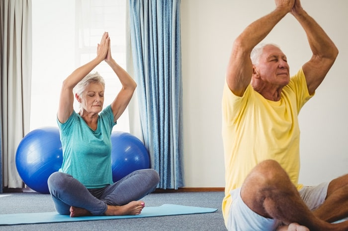 A female and male senior doing their meditative yoga pose on their yoga mats indoors.