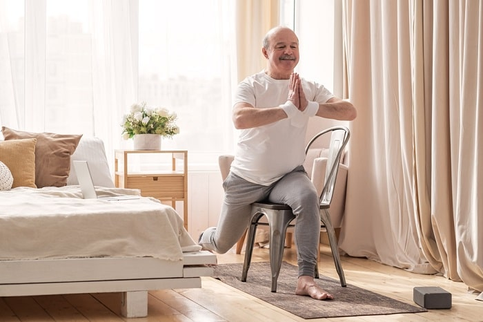 An elderly man practicing a yoga asana using a chair by the bed.
