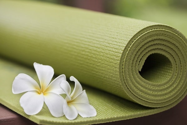 A green yoga mat with flowers beside it.