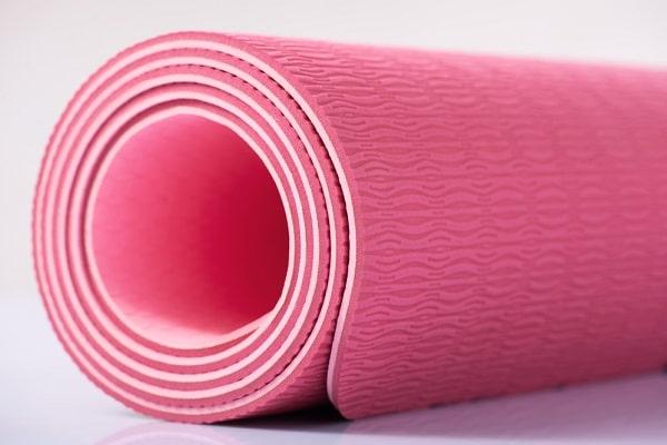 A pink rubber yoga mat.