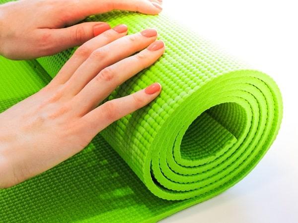 A woman rolling her green yoga mat.