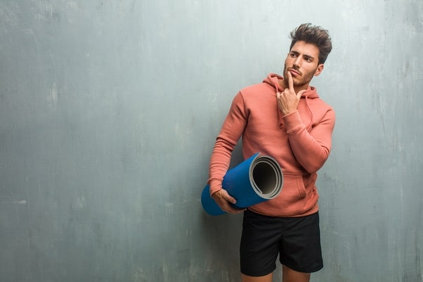 Pensive man standing against a gray wall, holding a blue yoga mat.