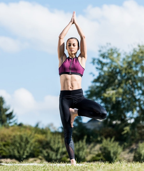 A woman doing a centering yoga pose outdoors.