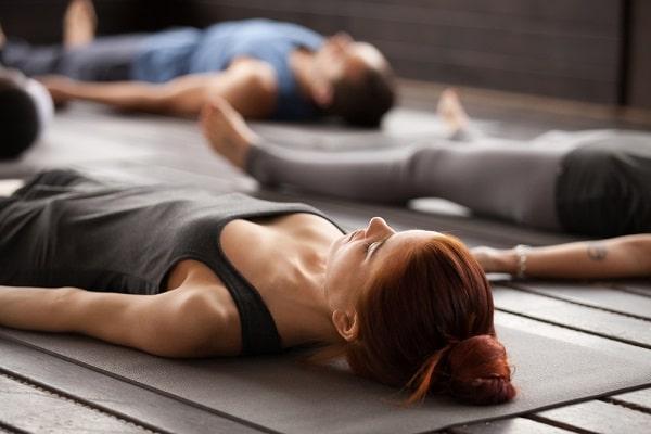 A group of people doing a Savasana yoga pose while meditating.