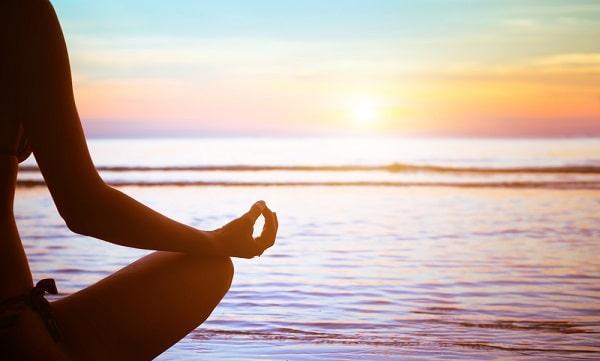 A woman meditating while doing a yoga pose, facing the sea.