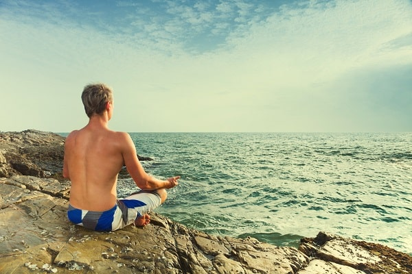 A man meditating while doing a yoga pose, facing the waves.