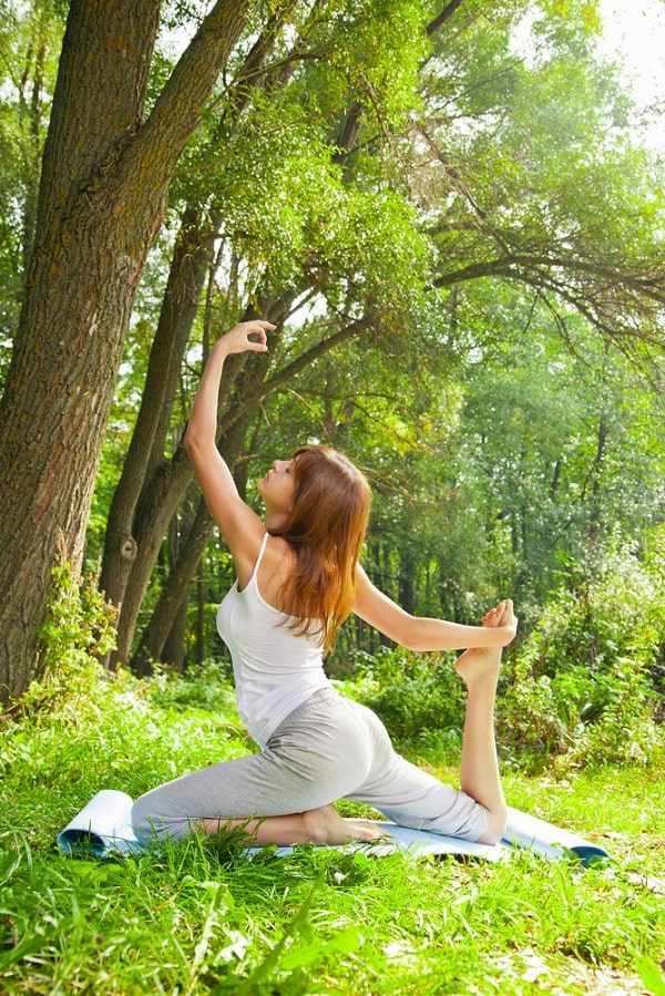 A woman doing a yoga pose in the park.