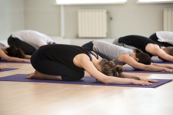 A group of women doing a yoga pose while in deep relaxation.