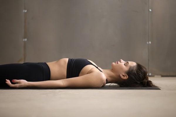 A woman doing a Savasana pose while meditating during yoga..