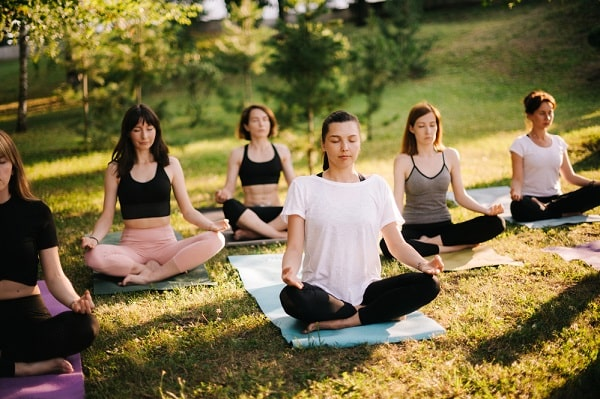A group of women doing their yoga meditation outdoors in Lotus Pose.