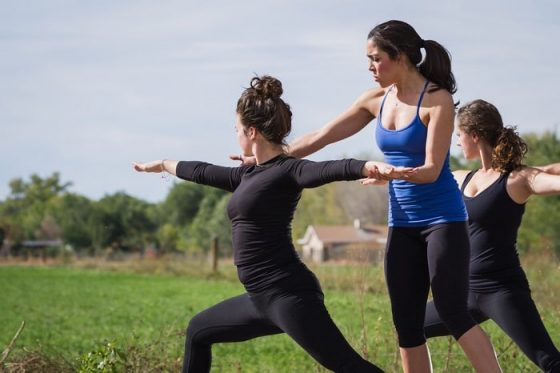 A female yoga instructor helping one of her students achieve the proper yoga pose during an outdoor yoga class.