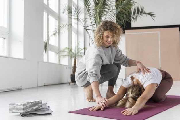 A female yoga instructor helping her student maintain a proper yoga pose on her purple yoga mat during an indoor yoga session.