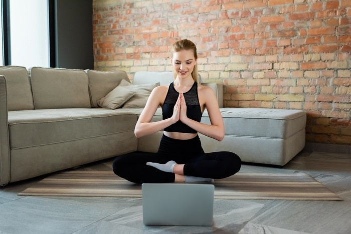 A woman in a sitting yoga pose on her yoga mat with her hands together, facing a laptop.