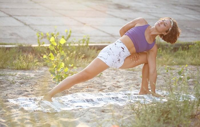 A woman practicing her yoga pose on a blanket outdoors.