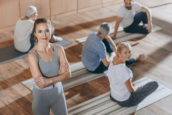 A female yoga instructor smiling with her arms crossed, with her students taking a break and conversing in the background.