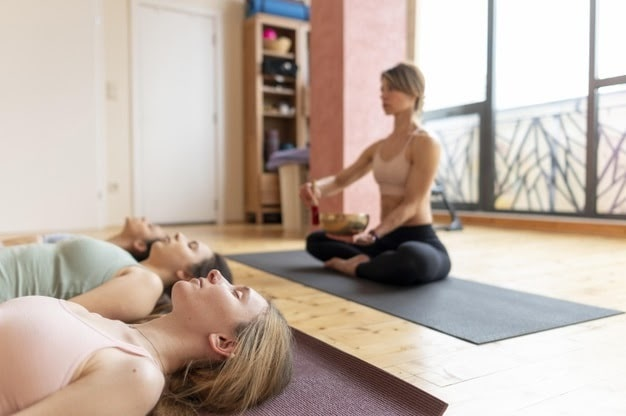 A female yoga instructor leading her students during a meditation session during yoga class.