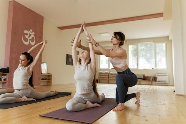 A female yoga instructor assisting her student to maintain proper form during a yoga pose on her yoga mat.