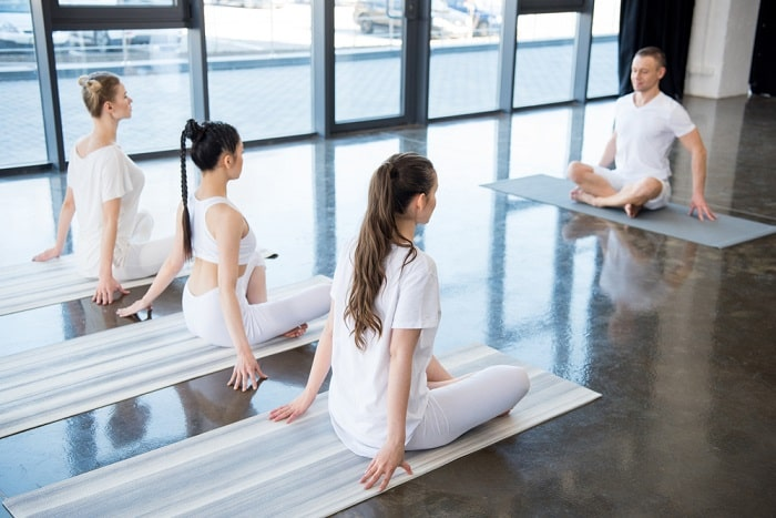 A male yoga instructor leading students to maintain proper posture during a yoga class indoors.