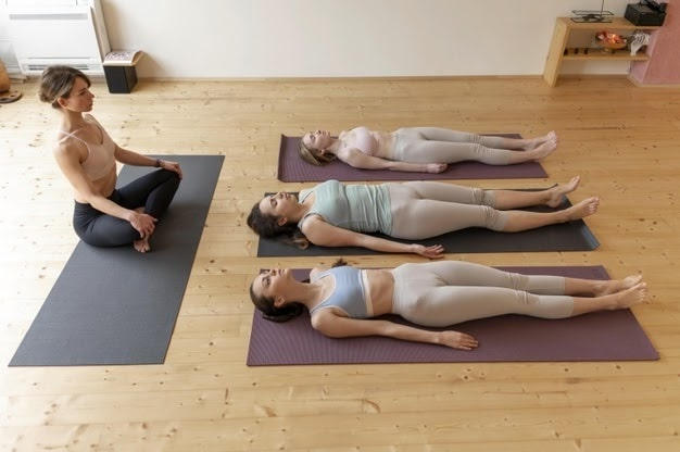 A female yoga instructor leading her class with students in a supine position.