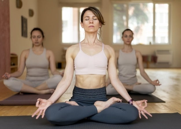 A female yoga instructor leading her students during a beginner asana pose with their eyes closed.