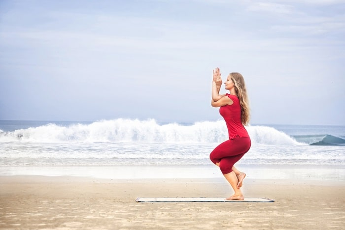 A woman in a red shirt and leggings doing Eagle Pose on a yoga mat by the shoreline with waves about to crash.