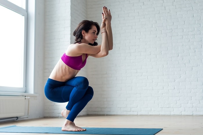 A woman doing Eagle Pose on a blue yoga mat at an indoor studio with white brick walls in the background.