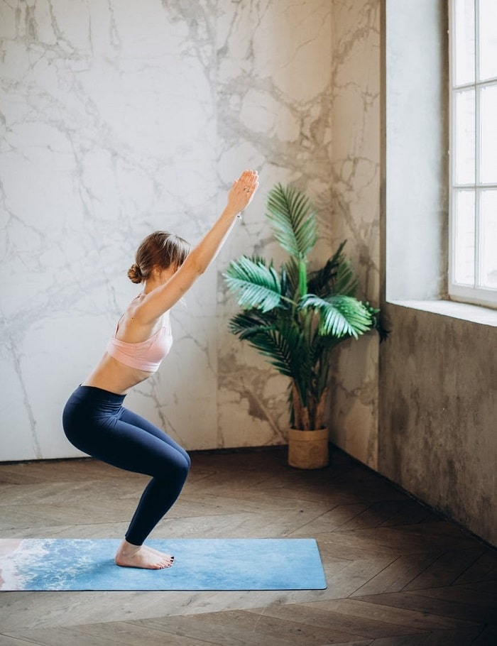 A woman facing the window while doing Chair Pose on a printed yoga mat inside a studio with marbled walls.