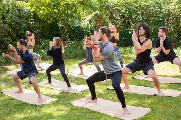 A yoga class doing Eagle Pose on their yoga mats outdoors with a grassy lawn and some foliage surrounding them.