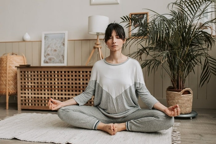 A woman doing a sitting yoga pose on a woven mat with her eyes closed and her back straight.