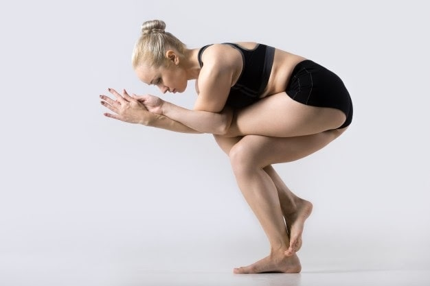 A woman doing a variation of Eagle Pose, balancing on a white floor, with a surrounding white backdrop.
