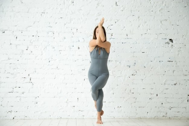 A woman in a gray one-piece outfit doing Eagle pose on a wooden floor, with surrounding white brick walls.