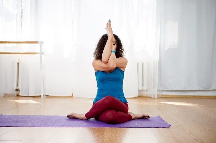 A woman preparing for Eagle Pose, while sitting down on a purple yoga mat with sheer curtains in the background.
