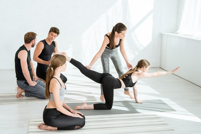 A female yoga instructor doing a mobility assessment to evaluate one of her students during a indoor yoga class.