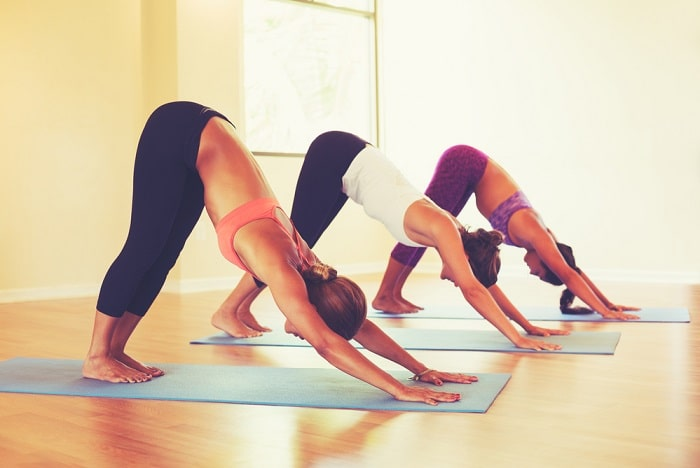 Students in a yoga class doing Downward-Facing Dog on their yoga mats at an indoor studio.