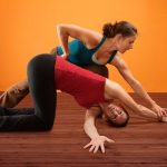 A female yoga instructor helping her student achieve the proper yoga pose on a wooden floor and against an orange background.