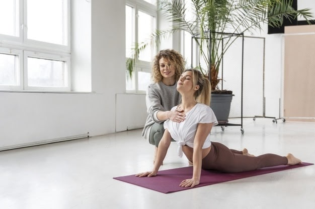 A female yoga instructor assisting her student maintain her yoga pose properly on a purple yoga mat.