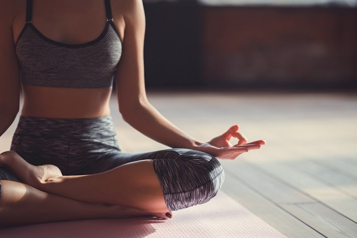 A woman in gray exercise clothes, doing a lotus pose while meditating on her yoga mat indoors.