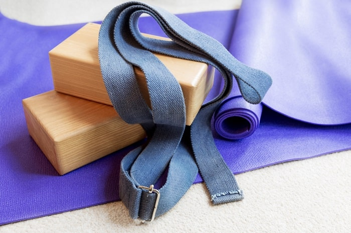 Various props for a yoga class on a purple-colored rug.