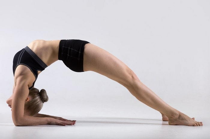 A woman balancing her whole body through a challenging yoga pose on a white floor against a white backdrop.