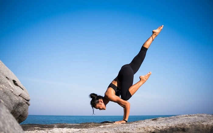 A woman doing an advanced-level standing yoga pose with her hands placed on a rocky surface with the blue sea and sky in the background.