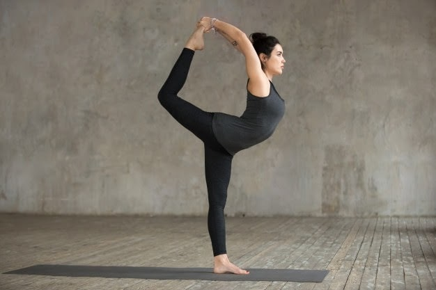 A woman doing Dancer's Pose on a dark gray yoga mat with concrete walls in the background.