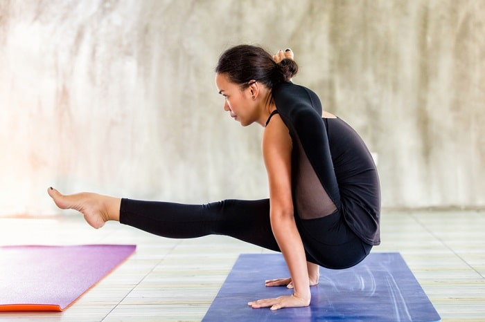 A woman doing an advanced-level yoga pose, balancing her whole body with her hands on a purple yoga mat against a concrete backdrop.