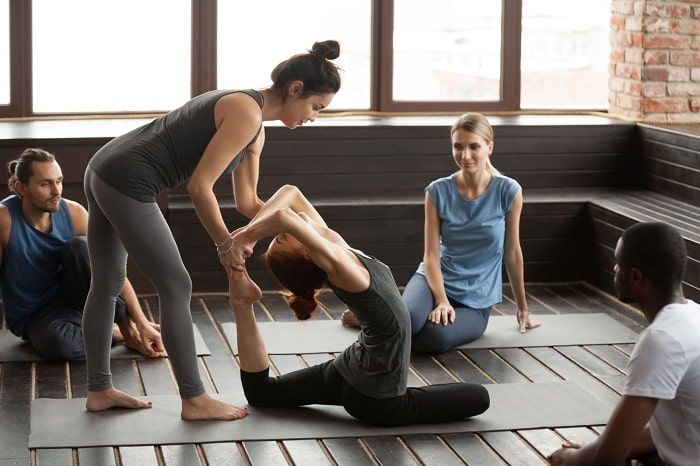 A female yoga instructor assisting one of her friends how to do a challenging yoga pose with the rest of her friends watching.