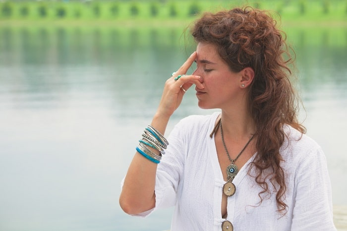 A woman in a white top and bohemian-style jewelry, practicing her pranayama yoga breathing exercise outdoors.