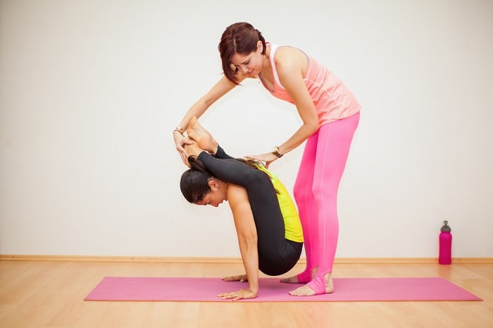 A female yoga instructor helping her student transition to a peak yoga pose on a pink yoga mat indoors.