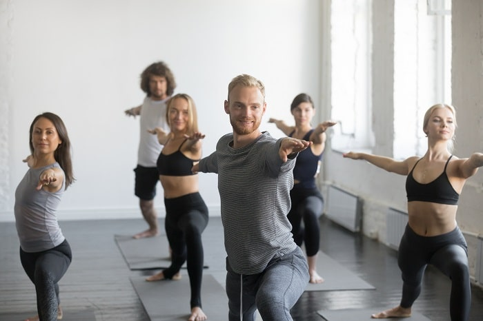 A male yoga instructor leading his yoga class during a beginner yoga pose on their gray yoga mats indoors..