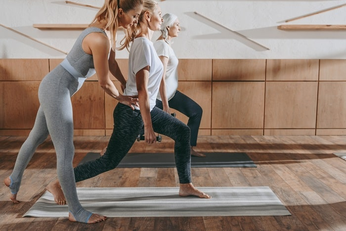 A female yoga instructor assisting one of her students in achieving the proper yoga pose while standing on a gray yoga mat in an indoor studio.